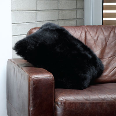Auskin Long Wool Black Cushion on a brown leather sofa