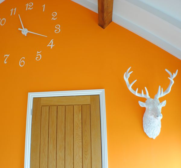 large white resin trophy wall stag head on orange wall with wooden door and white clock