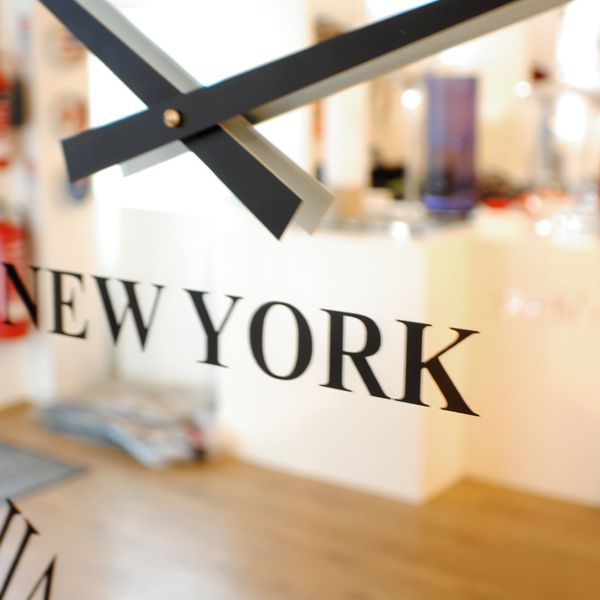 close up of black new york sign on mirror wall clock