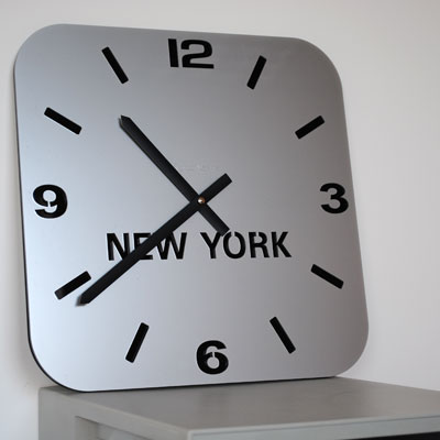 side view silver acrylic single timezone wall clock with black digits, hands and new york
