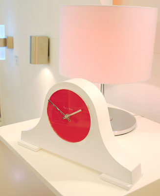 side view of classic shape mantel clock in white with cerise face