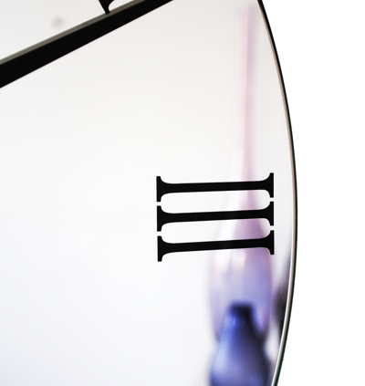 close up large round mirror wall clock with black roman numerals and black hands