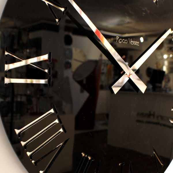 side view of large round gloss black modern acrylic wall clock with mirrored roman numerals and chrome hands