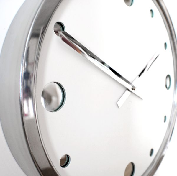 close up of white leather wall clock with chrome hands and polished metal case