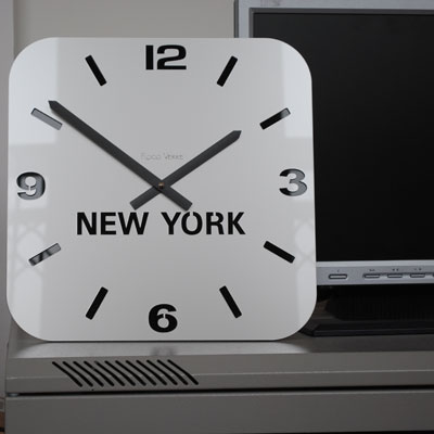 silver acrylic timezone clock in front of a computer monitor for scale