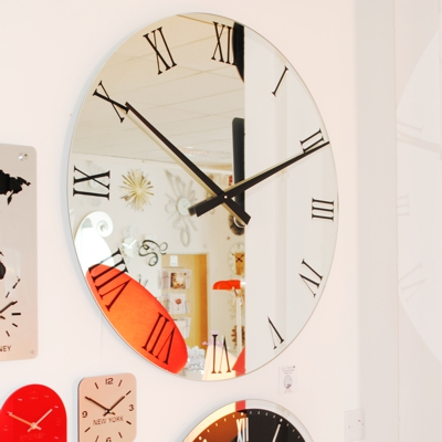 round black roman mirror wall clock and other clocks on a wall