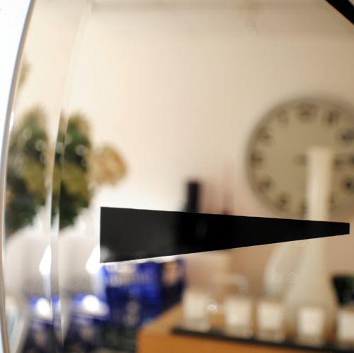 close up large round bevelled mirror wall clock with black digits and hands