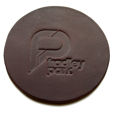 a round brown leather coaster with an embossed company logo
