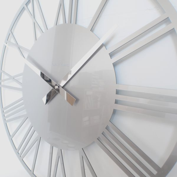 side view of a silver acrylic round skeleton wall clock