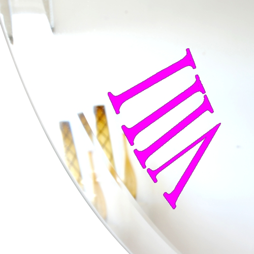 close up of pink roman numeral on bevelled mirror wall clock