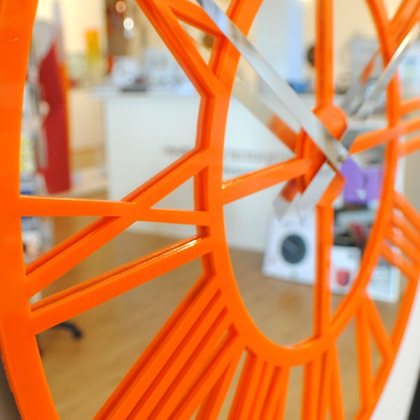 close up orange-gloss-skeleton-wall-clock
