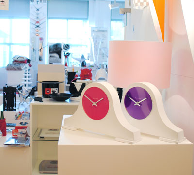 two classic shape white mantel clocks one with pink face the other with purple