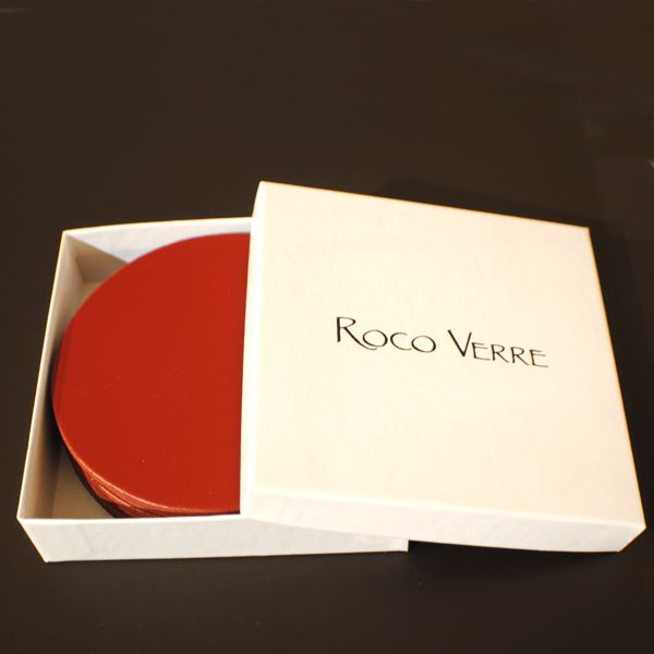 white gift box with lid open showing round red leather coasters inside