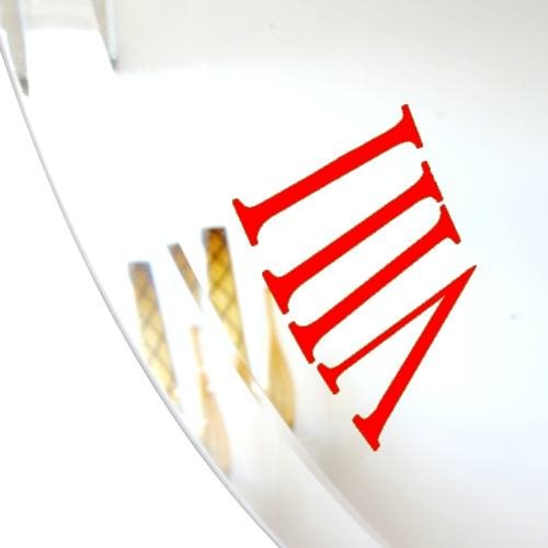 close up of red roman numeral on bevelled mirror wall clock