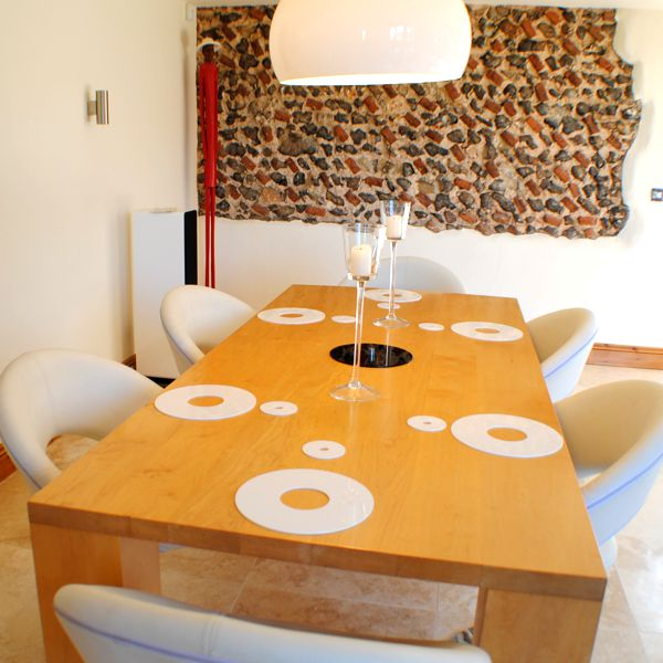 dining room with light wood table white place-mats and coasters on