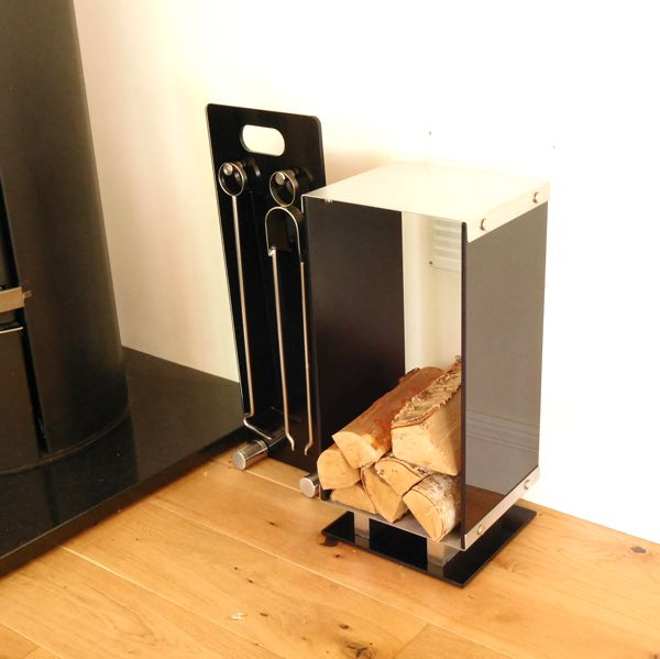 black glass and brushed steel contemporary log holder and fireside companion set on wooden floor next to log burner