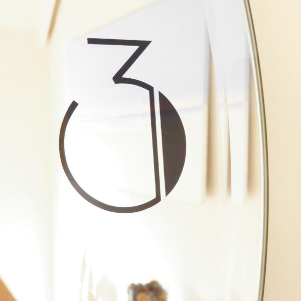 close up of a deco number on mirror wall clock