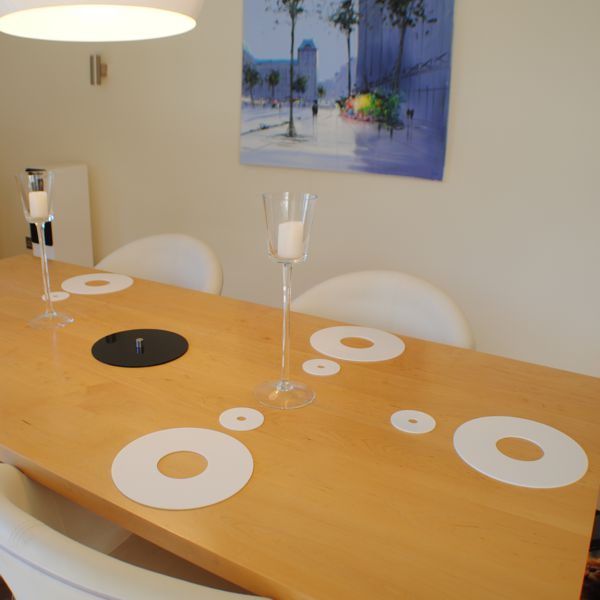 white coasters and place-mats on a light wood table with blue painting on the wall