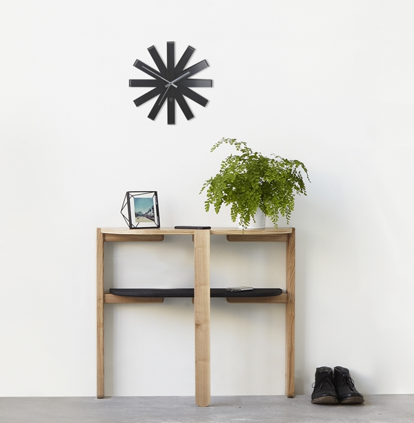 room set with wooden console table, green plant and black clock on the wall