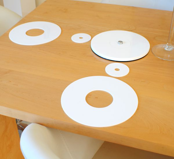 round white acrylic coasters and place-mats on a light wood table