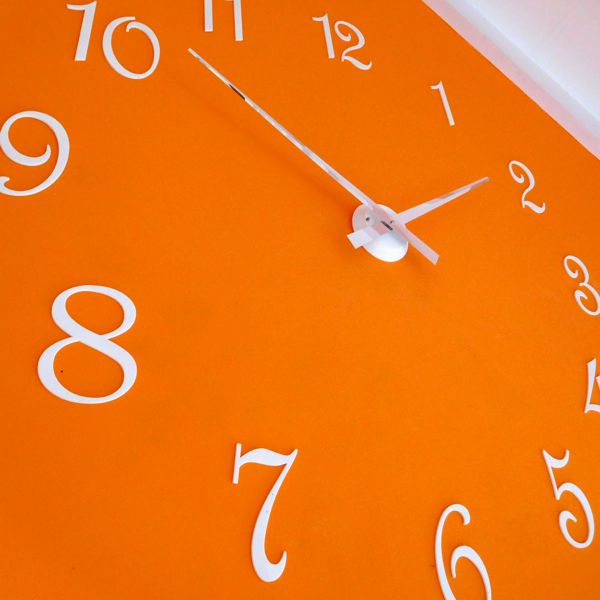 large hand clock with white numbers and chrome hands on an orange wall