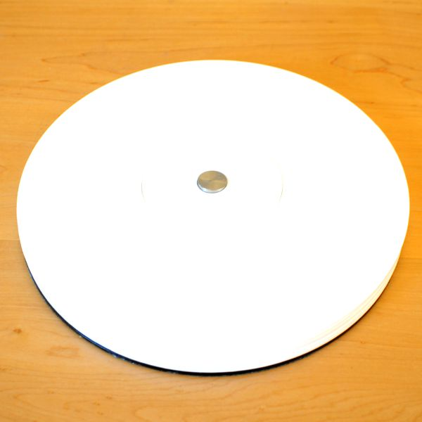 set of six round white acrylic coasters and place-mats on light wood table