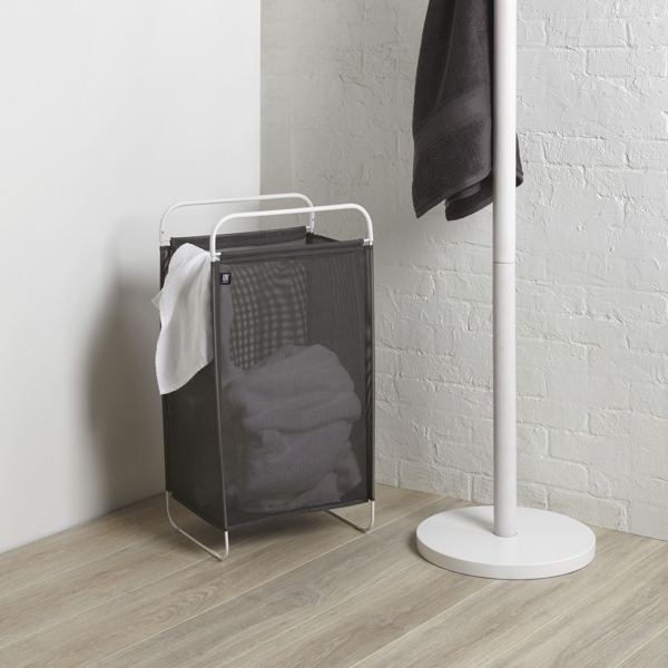 grey fabric and chrome metal laundry hamper next to a white coat stand